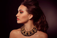 Fashion portrait of brown-eyes  woman.Gold jewelry. Orange yello Royalty Free Stock Images