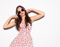 Fashion portrait of brunette girl with sunglasses. Long hair and blue eyes posing in bright summer short sexy dress nex to white b Stock Photo