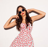 Fashion portrait of brunette girl with sunglasses. Long hair and blue eyes posing in bright summer short sexy dress nex to white b Stock Image
