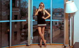 Fashion portrait of cheerful young blonde lady talking phone nea Stock Photos