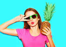 Fashion portrait cool girl in sunglasses and pineapple. Over blue background Royalty Free Stock Photos