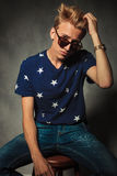 Fashion portrait of a cool young man fixing his hair Royalty Free Stock Photos