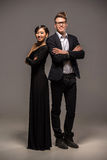 Fashion portrait of a couple. Full length photo of young  smiling couple dressed in formal clothing posing in the studio on dark background Stock Photo
