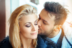 Fashion portrait of couple in love. Man kissing his woman in che royalty free stock photo