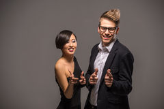 Fashion portrait of a couple. Young smiling couple dressed in formal clothing posing in the studio on dark background. Fashion portrait. Fun Stock Photos