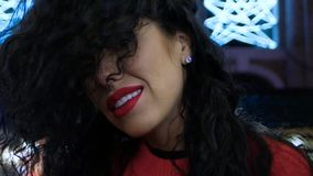 Fashion portrait of woman. Fashion portrait of curly young woman with red lips smiling to camera at night next to neon light. Nightlife atmosphere of girl stock video footage