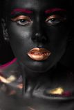 Fashion portrait of a dark-skinned girl with color make-up. Beauty face. Stock Photos