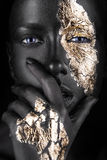 Fashion portrait of a dark-skinned girl with gold Royalty Free Stock Image