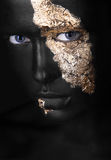 Fashion portrait of a dark-skinned girl with gold make-up. Beauty face. Stock Photo