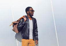Fashion portrait elegant african man wearing a sunglasses and black rock leather jacket with bag in the city, copy space empty stock photos