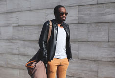Fashion portrait elegant african man wearing a sunglasses and black rock leather jacket with bag in city, copy space empty. Background Royalty Free Stock Photo