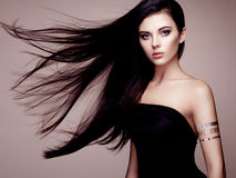 Fashion portrait of elegant woman with magnificent hair. Brunette girl. Perfect make-up. Girl in elegant dress. Flash tattoo gold stock photo