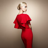 Fashion portrait of elegant woman in red dress. Fashion portrait of elegant woman with magnificent hair. Blonde girl. Perfect make-up. Girl in elegant red dress Royalty Free Stock Image