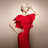 Fashion portrait of elegant woman in red dress. Fashion portrait of elegant woman with magnificent hair. Blonde girl. Perfect make-up. Girl in elegant red dress Stock Photography