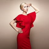 Fashion portrait of elegant woman in red dress. Fashion portrait of elegant woman with magnificent hair. Blonde girl. Perfect make-up. Girl in elegant red dress Royalty Free Stock Images