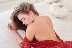 Fashion portrait of elegant young woman in red dress on bed in a luxurious interior Stock Photography