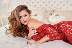 Fashion portrait of elegant young woman in red dress on bed in a luxurious interior.  Stock Images