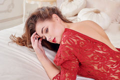 Fashion portrait of elegant young woman in red dress on bed in a luxurious interior Royalty Free Stock Photo
