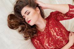 Fashion portrait of elegant young woman in red dress in luxurious interior royalty free stock photography