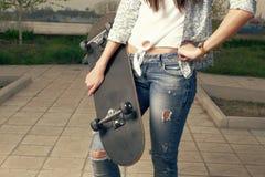 Fashion portrait of female holding a skateboard Stock Image