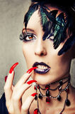Fashion portrait of female vampire. With gothic make up and long red nails royalty free stock images
