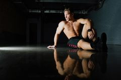 Fashion portrait of a fitness model of a bodybuilder man sitting on the mirror floor after a workout. Torso, shirtless, shorts. Dark background, beautiful Royalty Free Stock Image