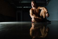 Fashion portrait of a fitness model of a bodybuilder man sitting on the mirror floor after a workout. Torso, shirtless, shorts. Dark background, beautiful Stock Photos