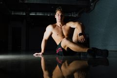 Fashion portrait of a fitness model of a bodybuilder man sitting on the mirror floor after a workout. Torso, shirtless, shorts. Dark background, beautiful Royalty Free Stock Photos