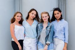 Fashion portrait of four beautiful attractive young women on the street stock image