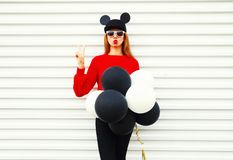 Fashion portrait funny woman in red knitted sweater with air balloons