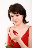 Fashion portrait of a girl. The Red rose in hands at the girl royalty free stock images