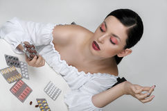 Fashion portrait of a girl who sorts the packs of medicines Stock Photos
