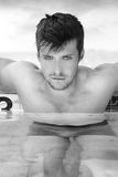 Man in pool. Fashion portrait of a gorgeous male model relaxing in luxurious swimming pool Stock Photo