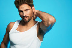 Fashion portrait of a gorgeous male model in white undershirt posing over isolated blue background. Good looking young man in white undershirt against blue stock photo