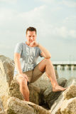 Fashion portrait of handsome man on the beach. Happiness summer vacation and people concept. Fashion portrait handsome man full length on the stone beach Royalty Free Stock Photography