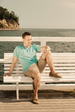 Fashion portrait of handsome man on bench outdoor Stock Photography