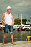 Fashion portrait of handsome man on pier against yachts Royalty Free Stock Photography