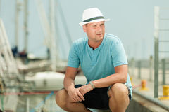 Fashion portrait of handsome man on pier against yachts Royalty Free Stock Photos