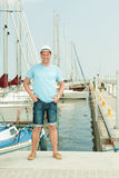 Fashion portrait of handsome man on pier against yachts Stock Images