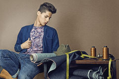 Fashion portrait of handsome young man with tools for sewing den Stock Photos