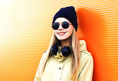 Fashion portrait happy blonde woman with headphones, sunglasses and black hat on orange colorful background in city Royalty Free Stock Images