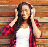 Fashion portrait happy smiling african woman with a headphones is enjoying listens to music Stock Photo