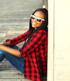 Fashion portrait happy smiling african woman wearing a red checkered shirt and sunglasses sitting Stock Photo