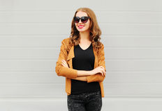Fashion portrait happy smiling woman with crossed arms wearing a sunglasses, jacket over grey Royalty Free Stock Photos