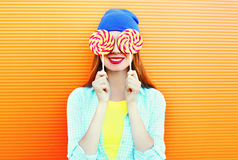 Fashion portrait happy smiling woman and lollipop is having fun over colorful orange Stock Photos