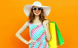 Fashion portrait happy smiling woman with shopping bags wearing colorful striped dress, summer straw hat posing on orange wall stock photography