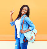 Fashion portrait happy smiling young african woman with backpack over orange Stock Photography
