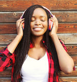 Fashion portrait of happy smiling young african woman with headphones enjoying listens to music Royalty Free Stock Photo