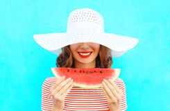 Fashion portrait happy smiling young woman is holding a slice of watermelon in a straw hat. Over a colorful blue background royalty free stock image