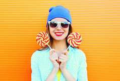 Fashion portrait happy smiling young woman with a lollipop on stick over colorful orange Stock Image